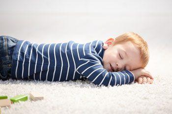 boy sleeping on carpet